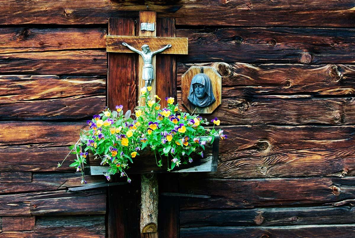 Almhütte mit wunderschön geschmücktem Kreuz.