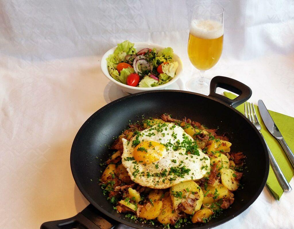 Das Spiegelei auf das Gröstl geben und mit viel Schnittlauch bestreuen - mit Salat und einem kühlen Bier servieren.