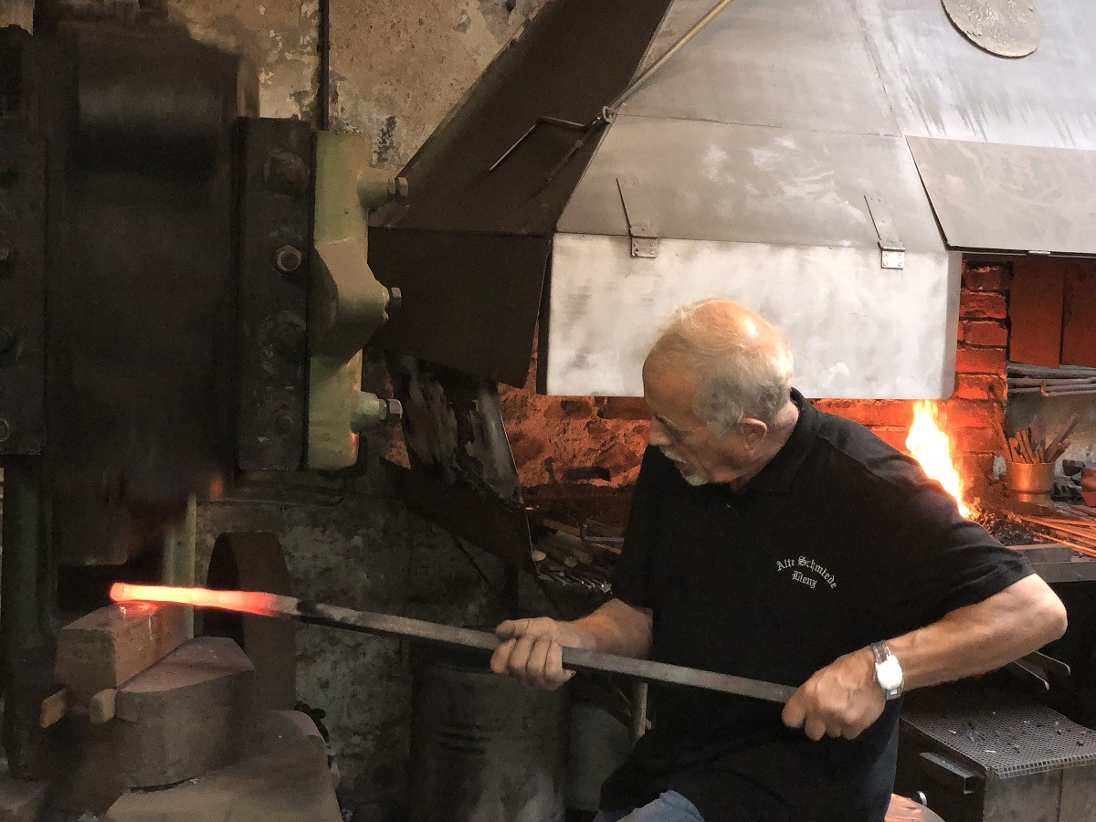 Rudl Duregger am Feuer der historischen Schmiede in Lienz.